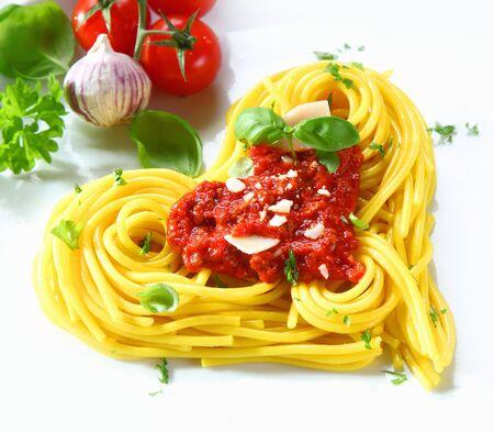 Gekookte spaghetti gerangschikt in een hartvorm overgoten met tomatensaus en verse basilicum