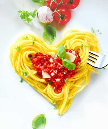 romantic dinner: Cooked spaghetti carefully arranged in a heart shape and topped with tomato sauce accompanied by raw ingredients to the side