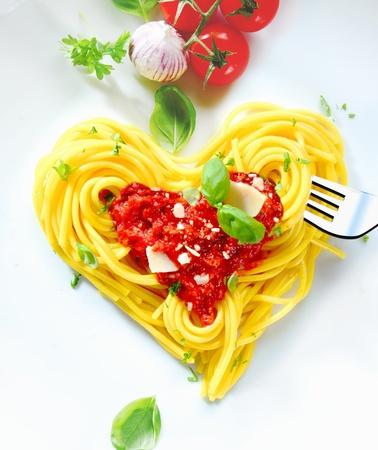 Gekookte spaghetti zorgvuldig gerangschikt in een hart vorm en overgoten met tomatensaus vergezeld van grondstoffen aan de kant