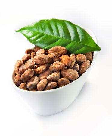 planta de cafe: Un tazón de cacao con una hoja verde aislado en blanco Foto de archivo