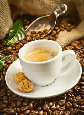 Espresso cup with fresh brewed coffee and beans