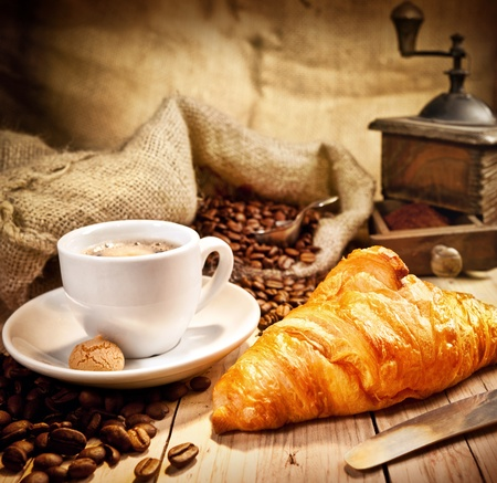 instant coffee: Coffee cup with a croissant and fresh coffee beanson a brown background Stock Photo