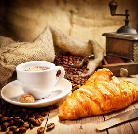 reggeli: Kávéscsésze a croissant és friss kávé beanson barna háttér Stock fotó