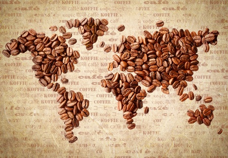 Fresh roasted coffee beans arranged in the shape of a world map on aged vintage paper with the word coffee in multiple languages. photo