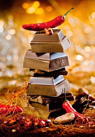 Conceptual image for red hot chocolate with a tower of chocolate cubes topped by a red hot chilli against a bokeh of festive lights photo
