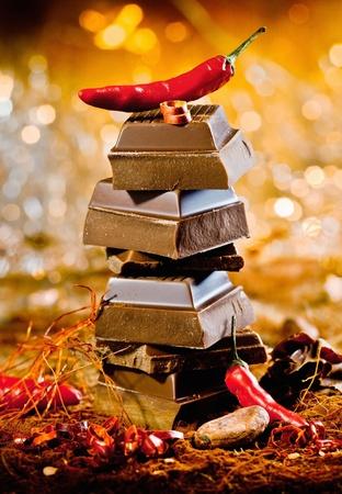 cioccolato natale: Immagine concettuale per il rosso cioccolata calda con una torre di cubi di cioccolato sormontato da un peperoncino rosso caldo contro un bokeh di luci di festa Archivio Fotografico