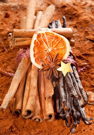 Bundle cinnamon and a bunch of vanilla beans with dried orange fruits on a brown cacao background. With a golden star and anise. photo