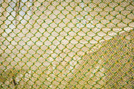 fish net: Abstract background of openframe knotted yellow green netting used by trawlers as a trawlnet when deep sea fishing Stock Photo
