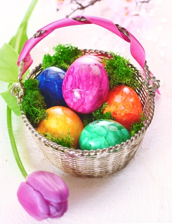 colorful still life: A basket full of colourful dyed marbled Easter eggs with a pretty pink tulip Stock Photo