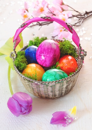 Overhead view of a round basket filled with colourful vibrant marbled Easter eggs alongside a pink tulip Stock Photo - 12640168