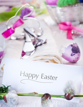 Easter table setting with focus to a plain white card inscribed Happy Easter