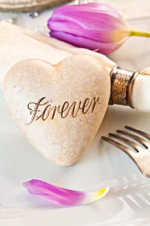 Romantic table setting with a heart inscribed with the word Forever, conceptual of an anniversary, wedding or Valentine photo