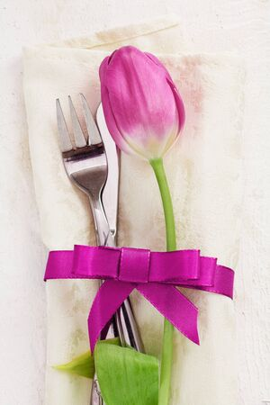 Napkin with tulip Flower. Dinner Table setting for two with a pink ribbon and a fork and a knife on wooden white background