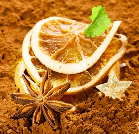 Dried orange slices with anise and a golden star on a brown background photo