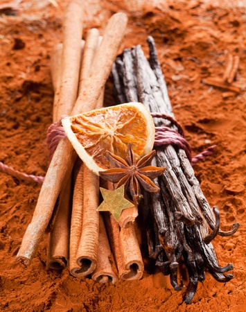 Bundle cinnamon and a bunch of vanilla beans with dried orange fruits on a brown cacao background photo