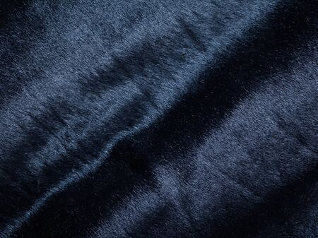 supple: Background of a dark piece of soft supple suede leather with wrinkles