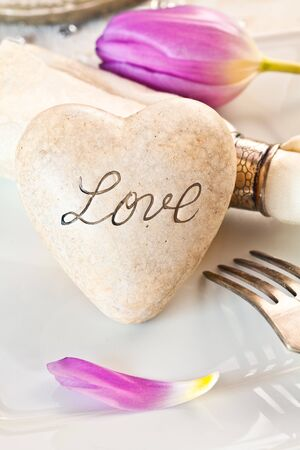 Love table setting with spring flower and stone heart inscribed with the word Love conceptual of valentines or a wedding card Stock Photo - 12640259