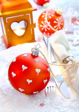 Red Xmas Bauble on snowy background with dishes an a napkin in front of a orange Lantern. photo