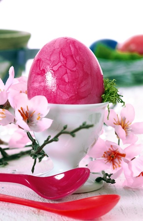 easteregg: Vibrant pink marbled Easteregg in an eggcup with pretty pink cherry blossom and spoons.