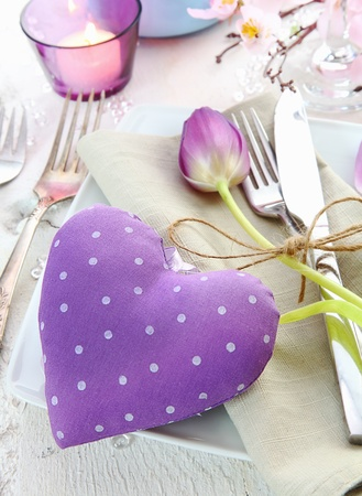 Delicate romantic table setting with a lilac fabric heart and tulip flanked by shiny silverware and a candle photo