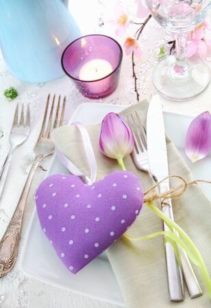 Elegant romantic place setting with a lilac heart for a sweetheart surrounded by silverware, a candle and delicate spring flowers