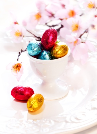 eggcup: An eggcup full of tiny colourful foil wrapped chocolate Easter Eggs with cherry blossom