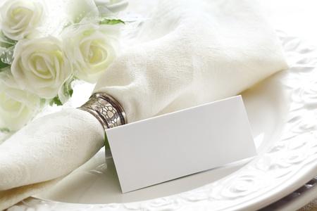 birthday flowers: Elegante witte bruiloft plaats instelling met mooie witte rozen en een lege kaart Stockfoto