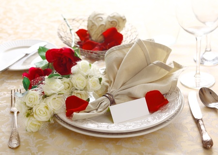 Pretty floral anniversary or Valentine table setting of red and white roses with a fanned napkin and blank card photo