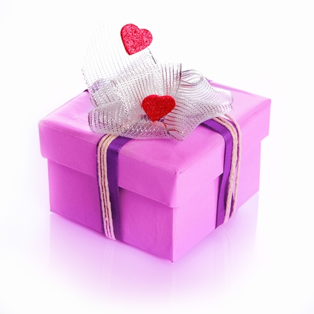 purple gift box decorated with hearts and a ribbon or bow isolated on white Stock Photo - 12640340