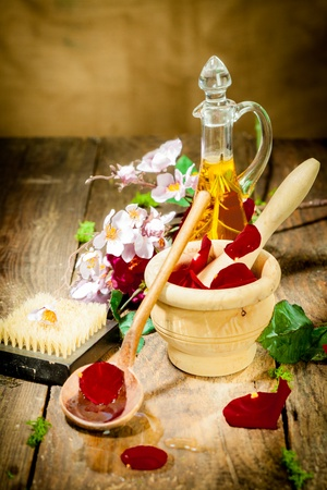 Wooden Mortar with Roses for spa and aroma therapy session on wooden floor photo