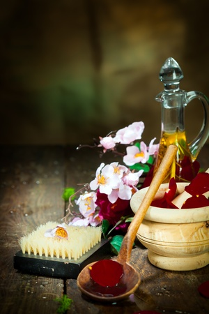 olfaction: Wooden Mortar with spring flowers for spa and aromatherapy session on wooden floor
