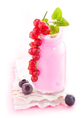 Healthy berry smoothie in a glass jar with delicious ripe red currants hanging over the side photo