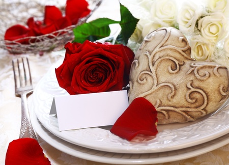 Wedding Place Setting with a place card, red and white roses and a heart photo
