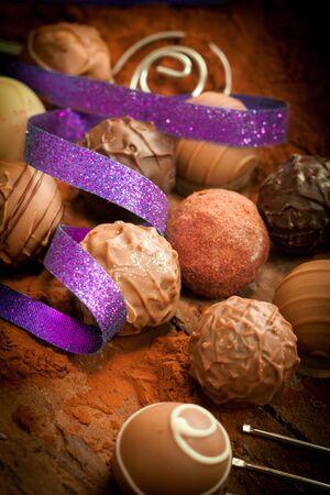 trufas de chocolate: Bombones con vi�eta y una cinta p�rpura sobre un fondo de cacao en polvo