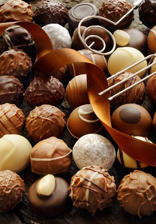 Background of an assortment of different decorative luxury chocolates with an ornamental ribbon