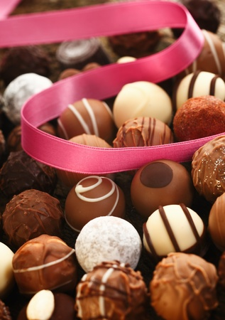 A decorative pink ribbon lies twirled over handmade spherical chocolates with different patterns in a gift and celebration concept photo