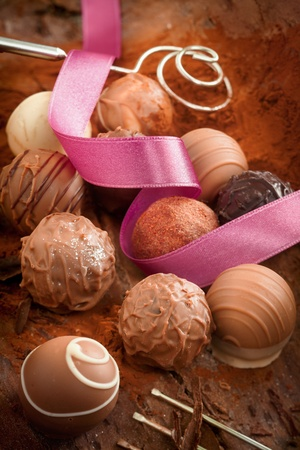 pralines: Decorative luxury handmade chocolates on a bed of cocoa powder with a spiralled pink ribbon for a celebration or gift Stock Photo
