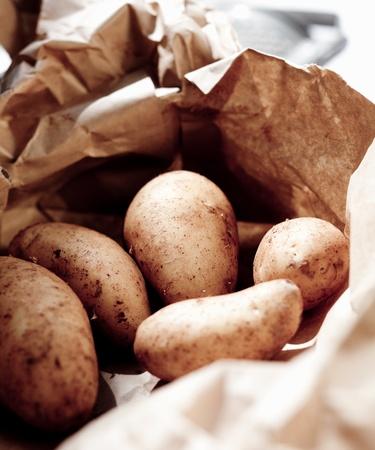 unwashed: Closeup di fresco patate lavate per la vendita al mercato in un sacchetto di carta marrone riciclabile