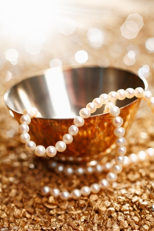 gold string: Necklace of matched pearls and a silver bowl with a festive sparkling bokeh of party lights