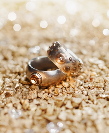 precious metal: Two Rings with jewels on a golden background maybe for a wedding card