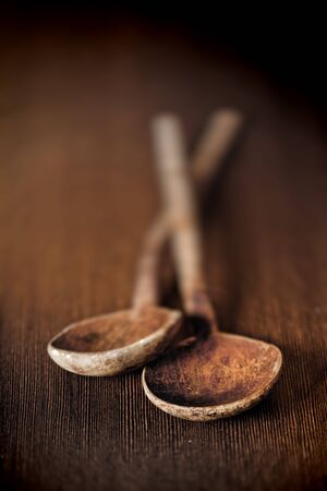 Background of two old wooden kitchen mixing spoons on a table top with bowls towards the camera and shallow depth of field photo