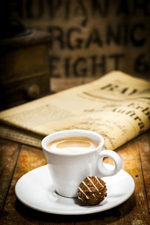 cafe bombon: Taza de café con leche rico con un bombón de chocolate en el platillo y un periódico doblado sobre la mesa detrás de un concepto de descanso para tomar café