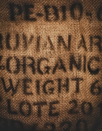 Vertical background of a twenty kilogram hessian coffee bag stamped and certified one hundred percent organic