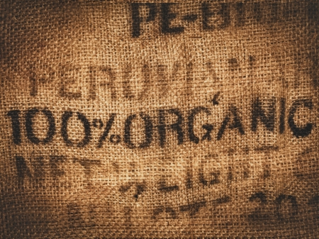 Background of a hessian coffee bag stamped and certified one hundred percent organic photo
