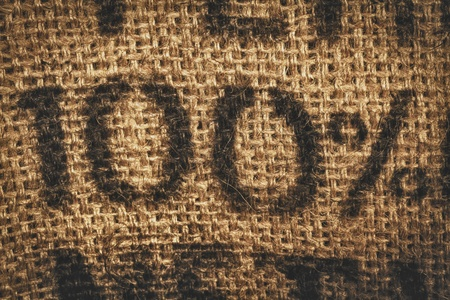 jute: Background of woven textured hessian stamped with one hundred percent - 100 percent - in numerals