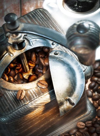 Retro wooden coffee grinder with its top open filled with coffee beans which have spilled out onto the table below photo