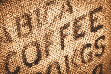 coffee sack: Close up of textured woven hessian fabric with the word Coffee stamped on it in a coffee background concept