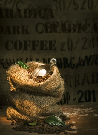 backround: Small rustic hessian bag filled to overflowing with fresh roasted coffee beans and topped with a small trowel and green leaves on a dark background with copyspace