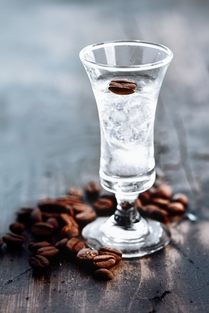 Tall glass with clear sambuca and coffee beans spilled around the base of the glass photo