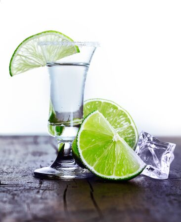 Tall glass with cool drink and lime slice with ice and lime on an outdoor table photo